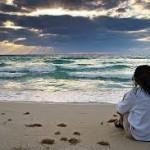 vrouw zittend op strand starend zee